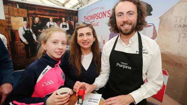 Press Eye - Belfast - Northern Ireland - 15th May 2019  First day of the Balmoral Show, in partnership with Ulster Bank.  Pictured at Balmoral Park, outside Lisburn, is (L-R) Leanne(13) and her mother Ann Marie Laverty from Mayobridge, Co. Down, with Thompson's Teas Jamie Thompson.  The mother and daughter were getting their Ulster Bank Food Trail card stamped.  Customers can visit different stands in the food hall getting their cards stamp which can be entered into a free draw.    Picture by Jonathan Porter/PressEye