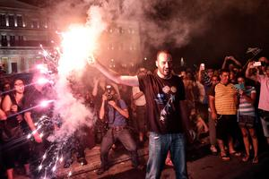 "ATHENS, GREECE - JULY 05:  People celebrate in front of the Greek parliament as Greek voters are expected to vote no in the Greek austerity referendum, on July 5, 2015 in Athens, Greece. The people of Greece are going to the polls to decide if the country should accept the terms and conditions of a bailout with its creditors. Greek Prime Minister Alexis Tsipras is urging people to vote ""a proud no"" to European creditors' proposals, and ""live with dignity in Europe"". 'Yes' campaigners believe that a no vote would mean financial ruin for Greece and the loss of the Euro currency.  (Photo by Milos Bicanski/Getty Images)"