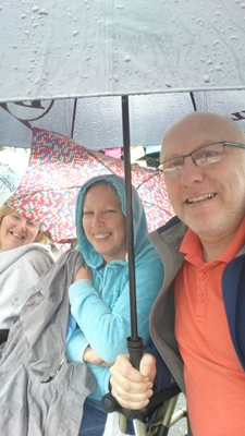 Vic and Jill Donaldson and Pam Currie, waiting for return parade in Portadown, despite a 'little shower'.