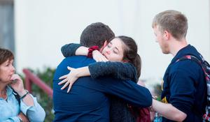 Mourners embrace following an open casket vigil for four Irish students who died Tuesday when a Berkeley apartment balcony collapsed, Friday, June 19, 2015, in Oakland Calif. (AP Photo/Noah Berger)