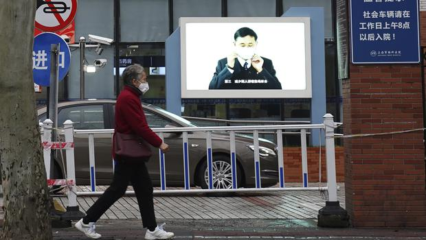 An elderly woman with a face mask walks past the entrance to the outpatient ward with a video display showing a public health message on wearing face masks in Shanghai (Erika Kinetz/AP)