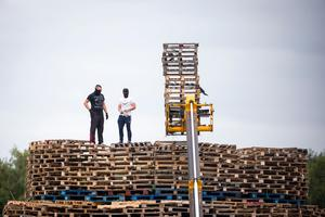 Masked men continue to build a bonfire at Inverary Playing Fields in Belfast. Liam McBurney/PA Wire