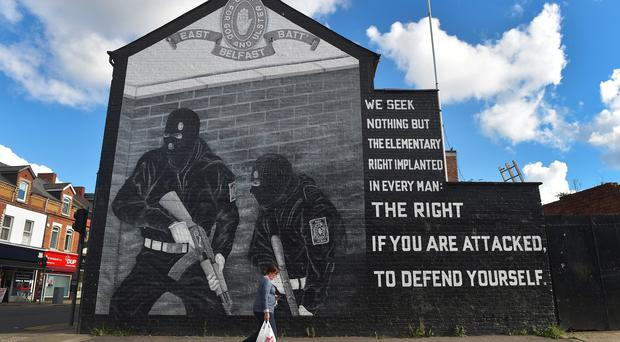 A woman carries her shopping past a loyalist paramilitary mural on the day that the new Loyalist Community Council was launched at the Park Avenue Hotel on October 13, 2015 in Belfast. Credit: Photo by Charles McQuillan/Getty Images