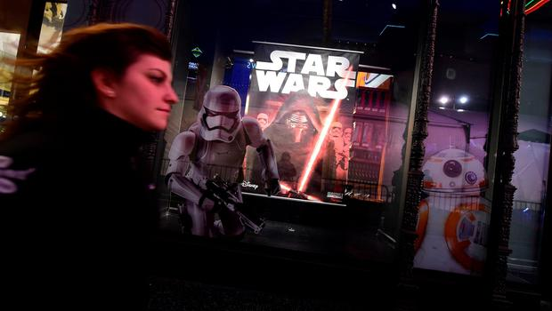 A woman rushes past a store selling Star Wars merchandise along Hollywood Boulevard for the premiere of the latest Star Wars film, 'The Force Awakens' in Hollywood, California on December 14, 2015. AFP PHOTO/ FREDERIC J. BROWNFREDERIC J. BROWN/AFP/Getty Images