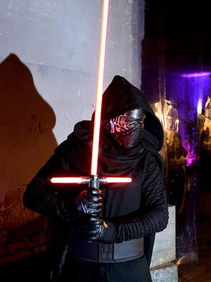 """A man wears a Star Wars character """"Kylo Ren"""" outfit during a party in downtown Rome on December 15, 2015 on the eve of the premiere of the Disney movie.     The latest installment of the Star Wars series opens in cinemas in France, Italy and other European countries at the start of a global rollout of the film, whose plot has been kept under wraps by producers Disney. / AFP / FILIPPO MONTEFORTEFILIPPO MONTEFORTE/AFP/Getty Images"""