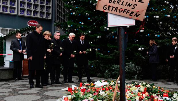 (L-R) Berlin's mayor Michael Mueller, German Chancellor Angela Merkel, German Interior Minister Thomas de Maiziere and German Foreign Minister Frank-Walter Steinmeier lay down flowers at a makeshift memorial for the victims of an attack on December 20, 2016 in front of the Kaiser-Wilhelm-Gedaechtniskirche (Kaiser Wilhelm Memorial Church) in Berlin, where a truck crashed into a Christmas market. Twelve people were killed and almost 50 wounded, 18 seriously, when the lorry tore through the crowd on December 19, 2016, smashing wooden stalls and crushing victims, in scenes reminiscent of July's deadly attack in the French Riviera city of Nice. / AFP PHOTO / Tobias SCHWARZTOBIAS SCHWARZ/AFP/Getty Images