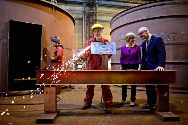 RENFREW, SCOTLAND - SEPTEMBER 16:  Deputy First Minister Nicola Sturgeon and Cabinet Secretary for Finance John Swinney, look on as 19 year old apprentice fabricator Craig McKee angle grinds a yes sign during their visit to Steel Engineering on September 16, 2014 in Renfrew, Scotland. With just two days of campaigning left before polling stations open and voters across the country will hold Scotlands future in their hands.  (Photo by Jeff J Mitchell/Getty Images)