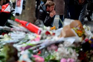 PARIS, FRANCE - NOVEMBER 16:  Members of the public look at floral tributes and messages at La Belle Equipe cafe on Rue de Charonne following Friday's terrorist attack on November 16, 2015 in Paris, France. France, currently observing three days of national mourning, will fall silent for one minute at 12pm local time today in an expression of solidarity with the victims of the terrorist attacks, which left at least 129 people dead and hundreds more injured.  (Photo by Jeff J Mitchell/Getty Images)