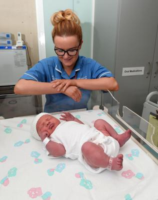 New Year babies at the Royal Victoria Hospital in Belfast - Baby McCaughran with Midwife Louise Ui Eachain