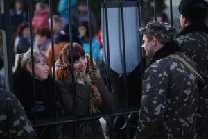 LUBIMOVKA, UKRAINE - MARCH 03:  Ukrainian soldiers at the Belbek military base talk friends and family members through the gates of the base entrance on March 3, 2014 in Lubimovka, Ukraine. Tensions at the base, where between 100 and 200 Ukrainian soldiers are stationed, are high as a 4pm deadline reportedly given by Russian troops for the Ukrainians to surrender passed and locals feared the Russians might attack tonight. Heavily-armed soldiers who are not displaying identifying insignia but are widely believed to be Russians have blockaded several Ukrainian military bases across Crimea.  (Photo by Sean Gallup/Getty Images)