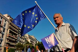 A pro-European Union protester holds an EU flag and a placard reading ''yes'' during a demonstration in Thessaloniki on July 2, 2015. Greece's government and international creditors raised the stakes on July 2 over a weekend referendum seen as decisive for the nearly insolvent EU country's political and financial future. While Prime Minister Alexis Tsipras has urged Greeks to vote 'No' to the austerity measures demanded by international creditors, opposition parties including the centre-right New Democracy are campaigning for a 'Yes' vote in the referendum on July 5. AFP PHOTO / SAKIS MITROLIDISSAKIS MITROLIDIS/AFP/Getty Images