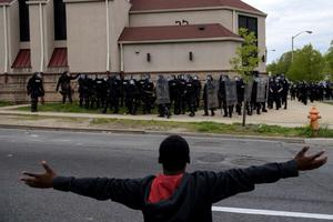 A protestor gestures before riot police on April 27, 2015 in Baltimore, Maryland on April 27, 2015 in Baltimore, Maryland.  Violent street clashes erupted in Baltimore after friends and family gathered for the funeral of Freddie Gray, a 25-year-old black man whose death in custody triggered a fresh wave of protests over US police tactics.  Police said at least seven officers were injured -- one of them was unresponsive -- as youths hurled bricks and bottles and destroyed at least one police vehicle in the vicinity of the shopping mall not far from the church where the funeral took place.  AFP PHOTO / BRENDAN SMIALOWSKIBRENDAN SMIALOWSKI/AFP/Getty Images