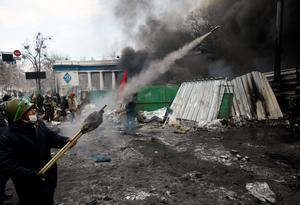 A protester aims fireworks at police during clashes, in central Kiev, Ukraine, Thursday Jan. 23, 2014. Thick black smoke from burning tires engulfed the downtown Ukrainian capital as an ultimatum issued by the opposition to the president to call early election or face street rage was set to expire with no sign of a compromise. (AP Photo/Darko Vojinovic)