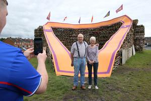 PACEMAKER, BELFAST, 11/7/2020: The sash my father wore! Norman and Lyn McCrea have their picture taken in front of the giant sash that adorns the Twelfth bonfire at Edgarstown in Portadown, Co Armagh  PICTURE BY STEPHEN DAVISON