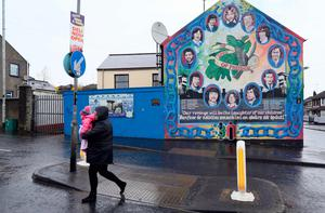 """A woman carries a child past a Republican mural in the Bogside neighbourhood of Derry in Northern Ireland on March 21, 2017 near the home of former deputy first minister Martin McGuinness, whose death was announced this morning.  Martin McGuinness, a one-time Irish Republican Army commander who later helped negotiate an end to the conflict in Northern Ireland, has died aged 66. His Sinn Fein party, which opposes British rule in Northern Ireland and was long considered the political arm of the IRA, announced the death in a statement on March 21, 2017, expressing """"deep regret"""".  / AFP PHOTO / Paul FAITHPAUL FAITH/AFP/Getty Images"""