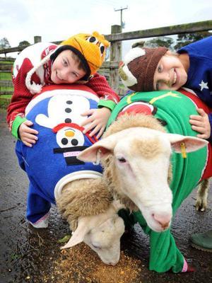 Luc Tedford from Belfast and Hector King from Holywood launch Save the Children's Christmas Jumper Day with some woolly models from County Antrim. Photo: Harrison Photography