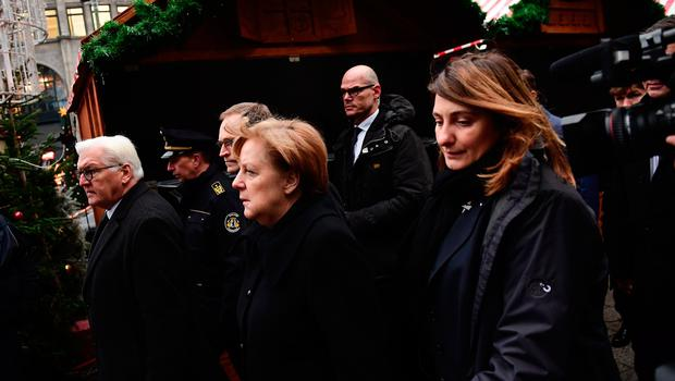 """German Chancellor Angela Merkel (C), German Foreign Minister Frank-Walter Steinmeier (L) and Berlin's mayor Michael Mueller (C) walk through the Christmas market of the Kaiser-Wilhelm-Gedaechtniskirche (Kaiser Wilhelm Memorial Church), the day after an attack at the nearby Christmas market in central Berlin, on December 20, 2016. German police said they were treating as """"a probable terrorist attack"""" the killing of 12 people when the speeding lorry cut a bloody swath through the packed Berlin Christmas market. / AFP PHOTO / Tobias SCHWARZTOBIAS SCHWARZ/AFP/Getty Images"""