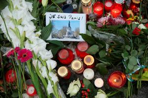 "BERLIN, GERMANY - NOVEMBER 16:  A hand-written message in French reads: ""I am Paris!"" among candles, messages and flowers left by mourners outside the French Embassy commemorating the victims of last Friday's terrorist attacks in Paris that have left over 130 people dead on November 16, 2015 in Berlin, Germany. Police are feverishly tracking down leads across Europe and looking for one of the attackers they think is still alive and on the run. The Islamic State (IS) has claimed responsibility for the attacks that were carried out by at least eight terrorists.  (Photo by Sean Gallup/Getty Images)"