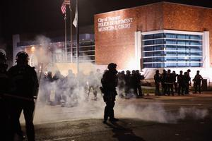 FERGUSON, MO - NOVEMBER 24:  Police guard the Ferguson police department as rioting erupts following the grand jury announcement in the Michael Brown case on November 24, 2014 in Ferguson, Missouri. Ferguson has been struggling to return to normal after Brown, an 18-year-old black man, was killed by Darren Wilson, a white Ferguson police officer, on August 9. His death has sparked months of sometimes violent protests in Ferguson. A grand jury today declined to indict officer Wilson.  (Photo by Scott Olson/Getty Images)