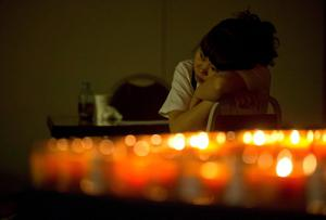 A woman with a relative onboard the missing Malaysia Airlines plane, MH370 rests near candles in a prayer room in Beijing, China, Friday, April 4, 2014. Crews searching for the missing Malaysia Airlines jet launched a targeted underwater hunt on Friday for the plane's black boxes along a stretch of remote ocean, with just days left before the devices' batteries are expected to run out. Chinese characters for words of consolations are seen at top right. (AP Photo/Ng Han Guan)
