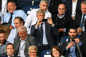 PARIS, FRANCE - JUNE 21: Arsne Wenger takes a picture of the Northern Ireland fans on his smartphone during the UEFA EURO 2016 Group C match between Northern Ireland and Germany at Parc des Princes on June 21, 2016 in Paris, France. (Photo by Charles McQuillan/Getty Images)