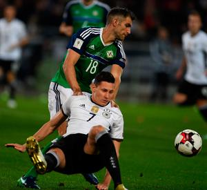 Stuck in: Aaron Hughes tussles with Julian Draxler during the clash between Northern Ireland and Germany in Hannover
