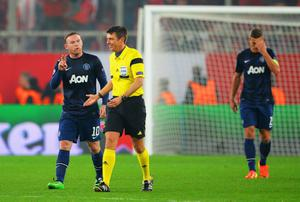 PIRAEUS, GREECE - FEBRUARY 25:  Wayne Rooney (L) of Manchester United talks to match referee Gianluca Rocchi during the UEFA Champions League Round of 16 first leg match between Olympiacos FC and Manchester United at Karaiskakis Stadium on February 25, 2014 in Piraeus, Greece.  (Photo by Michael Regan/Getty Images)