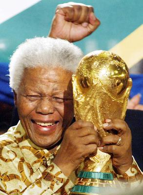 FILE - In this May 15, 2004 file photo, former South African President Nelson Mandela lifts the World Cup trophy in Zurich, Switzerland, after FIFA's executive committee announced that South Africa would host the 2010 World Cup soccer tournament.   South Africa's president Jacob Zuma says, Thursday, Dec. 5, 2013, that Mandela has died. He was 95.  (AP Photo/Michael Probst, File)