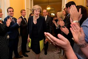 Staff applaud as new British Prime Minister Theresa May and her husband Philip John walk into 10 Downing Street in London, on July 13, 2016 after meeting Queen Elizabeth II and accepting her invitation to become Prime Minister and form a new government. Theresa May took office as Britain's second female prime minister on July 13 charged with guiding the UK out of the European Union after a deeply devisive referendum campaign ended with Britain voting to leave and David Cameron resigning. / AFP PHOTO / POOL / Stefan RousseauSTEFAN ROUSSEAU/AFP/Getty Images
