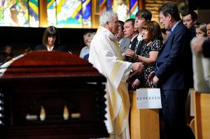 Monsignor Dan Whelton gives his condolences to the Burke family from right, father Paul and mother Paula Burke and brother Gavin Burke during funeral services for Olivia Burke, 21, and Ashley Donohoe, 22, at St. Joseph Catholic Church in Cotati, Calif., on Saturday, June 20, 2015. The two woman were among the several people killed on Tuesday when a balcony snapped off the fifth floor of a Berkeley apartment building during a birthday party. (AP Photo/Michael Short)