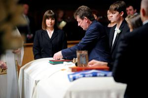 Paul Burke places items on top of his daughter's casket during a service for Olivia Burke, 21, and Ashley Donohoe, 22, at St. Joseph Catholic Church in Cotati, Calif., on Saturday, June 20, 2015.  The two woman were among the several people killed on Tuesday when a balcony snapped off the fifth floor of a Berkeley apartment building during a birthday party. (AP Photo/Michael Short)