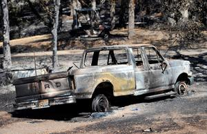 A burned out truck sits at a residence as a wildfire burns near Clearlake, Calif., Monday, Aug. 3, 2015. Officials called for evacuations Monday as numerous homes were threatened by the flames. (AP Photo/Josh Edelson)