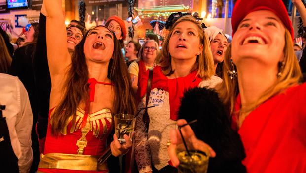 LONDON, ENGLAND - NOVEMBER 08:  A Democrat dressed as Wonder Woman and her friends celebrate Hillary Clinton winning the state of Vermont at the Democrats Abroad US election night party at Marylebone Sports Bar and Grill on November 8, 2016 in London, England. Americans have gone to the polls today, November 8, to elect the 45th President of the United States. Democratic presidential candidate Hillary Clinton, if elected, would be the first woman president in American history. Clinton is running against Republican presidential candidate Donald Trump. (Photo by Chris J Ratcliffe/Getty Images)