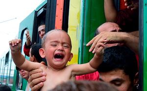A migrant holds a crying boy out of a local train coming from Budapest and heading to the Austrian border, that has been stopped in Bicske, west of the Hungarian capital on September 3, 2015. AFP/Getty Images