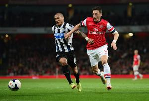 LONDON, ENGLAND - APRIL 28:  Mesut Oezil of Arsenal battles with Yoan Gouffran of Newcastle United during the Barclays Premier League match between Arsenal and Newcastle United at Emirates Stadium on April 28, 2014 in London, England.  (Photo by Jamie McDonald/Getty Images)