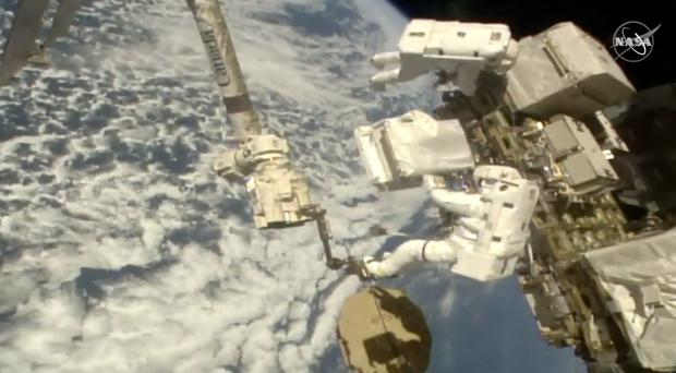 Italian astronaut Luca Parmitano, lower right, holds a bundle of new pumps during a spacewalk (Nasa/AP)
