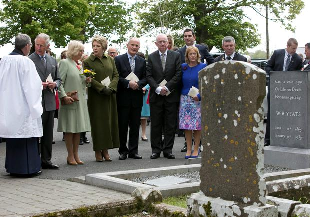 The Prince of Wales (2nd left) and The Duchess of Cornwall (3rd left) at the grave of WB Yeats after attending a peace and reconciliation prayer service at St. Columba's Church in Drumcliffe on day two of a four day visit to Ireland. PRESS ASSOCIATION Photo. Picture date: Wednesday May 20, 2015. See PA story ROYAL Ireland. Photo credit should read: Colm Mahady/PA Wire
