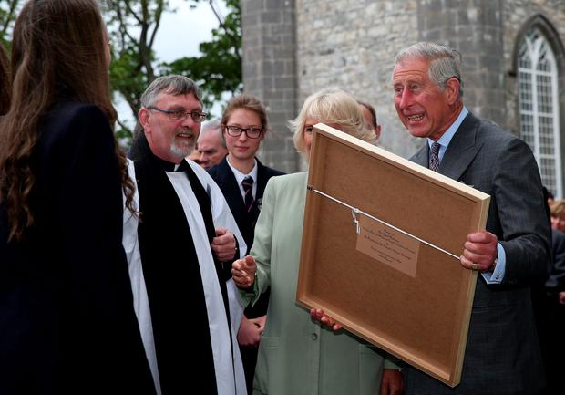 The Prince of Wales and the Duchess of Cornwall receive a painting after a service of peace and reconciliation at St. Columba's Church in Drumcliffe on the second day of a four day visit to Ireland. PRESS ASSOCIATION Photo. Picture date: Wednesday May 20, 2015. See PA story ROYAL Ireland. Photo credit should read: Brian Lawless/PA Wire