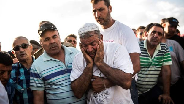 "YAHUD MONOSON, ISRAEL - JULY 16:  Mourners weep for Dror Khenin during his funeral on July 16, 2014 in Yahud Monoson, Israel. Yesterday Khenin was the first Israeli to be killed by a Hamas motar as he offered food to Israeli soldiers working near the Erez border crossing between Israel and Gaza. As Operation ""Decisive Edge"" enters its ninth day, over 200 Palestinians have been killed in Israeli missile strikes.  (Photo by Andrew Burton/Getty Images)"