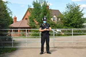 A police officer wearing a face mask at Rook Row Farm (Jacob King/PA)