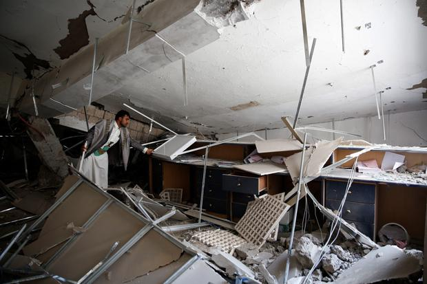 An employee inspects a room inside the Chamber of Trade and Industry headquarters after it was hit by a Saudi-led airstrike in Sanaa, Yemen, Tuesday, Jan. 5, 2016. (AP Photo/Hani Mohammed)