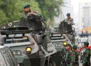 Indonesian soldiers man an armored vehicle as they guard near the site where an attack occurred in Jakarta, Indonesia Thursday, Jan. 14, 2016. Attackers set off explosions at a Starbucks cafe in a bustling shopping area in Indonesia's capital and waged gunbattles with police Thursday, leaving bodies in the streets as office workers watched in terror from high-rise windows. (AP Photo/Dita Alangkara)