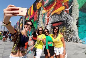 People pose for photographs on Olympic Boulevard by mural in the port district, that has been regenerated for the Olympic Games, Rio de Janeiro, Brazil. PRESS ASSOCIATION Photo. Picture date: Friday August 19, 2016. Photo credit should read: Martin Rickett/PA Wire. RESTRICTIONS - Editorial Use Only.