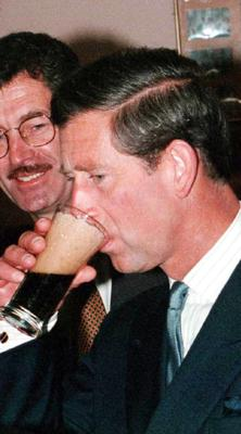 Charles sips a glass of Guinness, watched by Irish deputy prime minister Dick Spring during his 1995 visit (Martin Keene/PA)