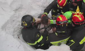 This frame from video shows Italian firefighters extracting a woman alive from under snow and debris of an hotel that was hit by an avalanche on Wednesday, in Rigopiano, central Italy, Friday, Jan. 20, 2017. (Italian Firfighters/ANSA via AP)