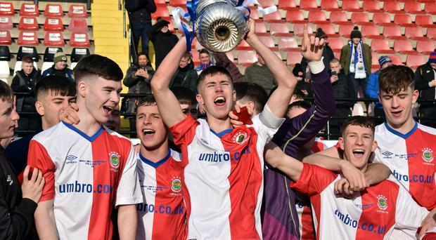 Linfield's Trai Hume lifts the trophy.