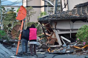 A couple heads to their house in Mashiki, Kumamoto prefecture on April 16, 2016.   A powerful earthquake hit southern Japan early April 16, authorities said, sending panicked residents out of their homes in a region where nerves were already frayed by a swarm of strong shaking. / AFP PHOTO / KAZUHIRO NOGIKAZUHIRO NOGI/AFP/Getty Images