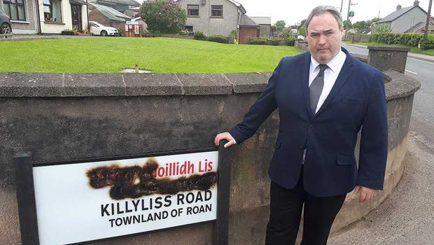 Fermanagh & South Tyrone MLA Colm Gildernew pictured with a vandalised sign.