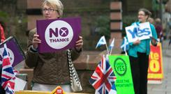 Yes and No supporters react to motorists passing the Church Hill Theatre polling place in Morningside on September 18, 2014 in Edinburgh, Scotland (Photo by Matt Cardy/Getty Images)