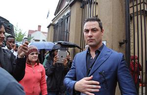 Carl Pistorius, right, the brother of Oscar Pistorius walks outside the high court before the start of his brother's trial in Pretoria, South Africa, Monday, March 3, 2014. Pistorius is charged with murder with premeditation in the shooting death of girlfriend Reeva Steenkamp in the pre-dawn hours of Valentine's Day 2013. (AP Photo/Schalk van Zuydam)